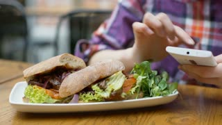 View of healthy food lying on table and girl's hands using smartphone, steadycam
