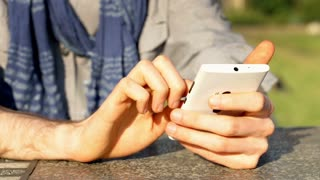 View of male hands texting sms or browsing internet on smartphone