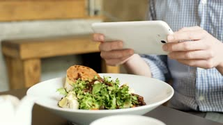 View of man's hands holding tablet and doing photos of healthy food, steadycam s