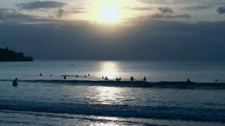 View of people swimming in the sea while sunsetting, slow motion shot at 240fps