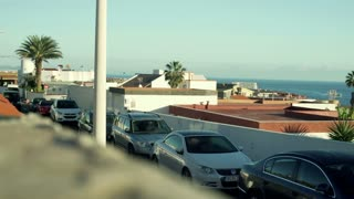 View of the seaside town and cars standing in the street