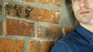 View of thoughtful man standing next to the brick wall, steadycam shot
