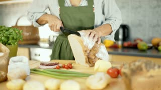 View of woman standing in the kitchen and cutting bread into slices, dolly shot