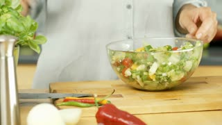 Woman adding olive oil to the freshly made, vegetable salad, dolly shot