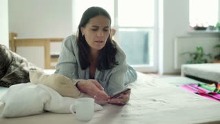 Woman calling and receiving bad news while lying on bed