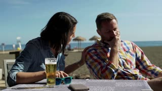Woman comforting her boyfriend in the restaurant on the beach