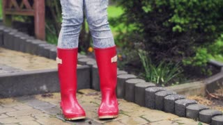 Woman dancing on pavement and wearing red rain boots