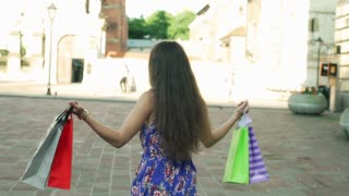 Woman dancing with shopping bags on the square, steadycam shot