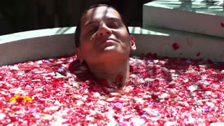 Woman diving in the bath full of flowers, slow motion shot