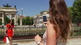 Woman doing photo of her friend next to triumphal arch, steadycam shot