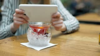 Woman doing photos of facy drink on tablet while sitting in the cafe