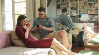 Woman drinking coffee and man using smartphone on the sofa