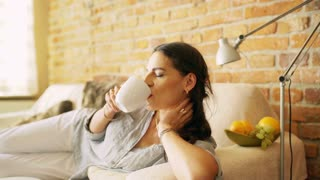 Woman drinking coffee and smiling to the camera