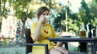 Woman drinking coffee in the outdoor cafe and answers cellphone