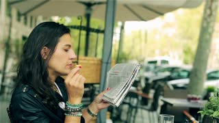 Woman eating lunch and reading newspaper in the street cafe, steadycam shot