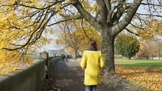 Woman having a walk in the autumnal park next to the river
