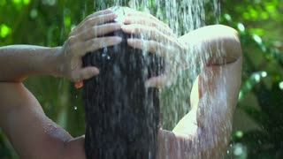 Woman having shower and washing hair in the garden, slow motion shot at 240fps