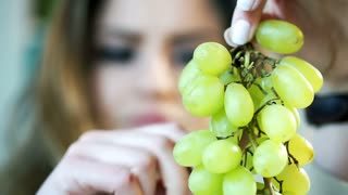 Woman holding bunch on grapes and eating them, steadycam shot