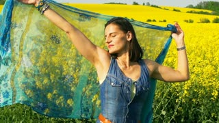 Woman holding scarf in rapseed's field, steadycam shot, slow motion shot at 240f