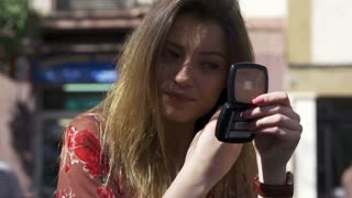 Woman improving makeup in street cafe, steadycam shot