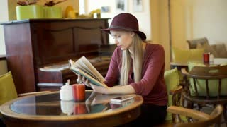 Woman in classic clothes reading book in a vintage cafe, steadycam shot