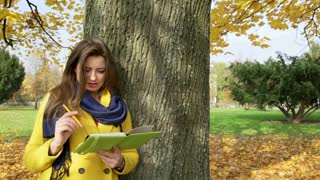 Woman leaning on tree and write something in the journal