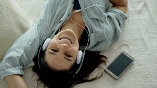 Woman listening music and smiling to the camera while lying on bed