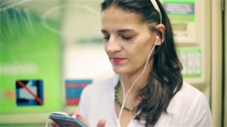 Woman listening music on earphones in the subway, steadycam shot