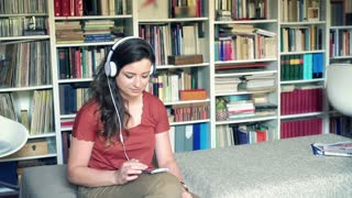 Woman listening music on headphones and smiling to the camera, steadycam shot