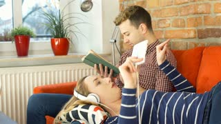 Woman listening music while her boyfriend reading book, steadycam shot