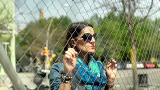 Woman looking pensive and holding wire fence, steadycam shot