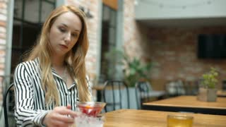 Woman looks pensive while sitting in the cafe and drinking fancy beverage