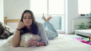 Woman lying on bed and drinking coffee at home