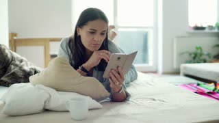 Woman lying on bed in the morning and using smartphone