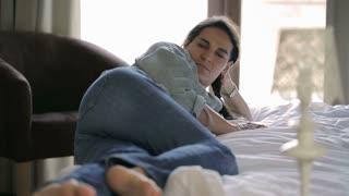 Woman lying on bed with barefoot, steadycam shot
