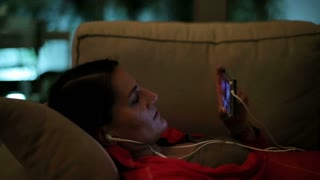 Woman lying on sofa and watching film on cellphone, closeup.