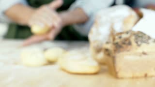 Woman making rolls from dough in the kitchen on the wooden table, dolly shot