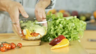 Woman making salad and mixing vegetables in a bowl, dolly shot