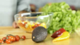 Woman open avocado and taking seed from the insie by using knife, dolly shot