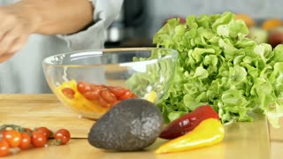 Woman peeling avocado and making delicious, healthy salad in the kitchen, dolly