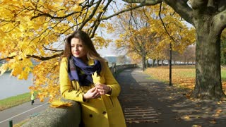 Woman playing with maple leaf and smiling to the camera in the autumnal park