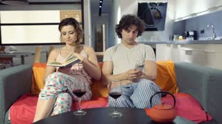 Woman reading book and her boyfriend browsing internet on smartphone