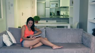 Woman reading book on the sofa at home