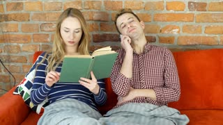 Woman reading book while her boyfriend chatting on cellphone, steadycam shot