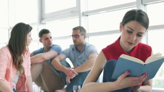 Woman reading book while her friends having a good talk