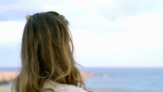 Woman relaxing at the sea and enjoys the view, steadycam shot