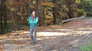 Woman relaxing in the autumnal forest and smiling to the camera