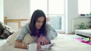 Woman relaxing on the bed and reading book at home