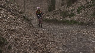 Woman riding on bike up the hill, steadycam shot