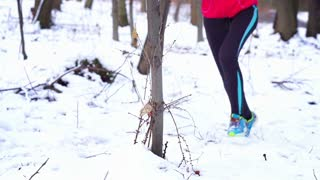 Woman running at winter in the forest, steadycam shot, slow motion shot